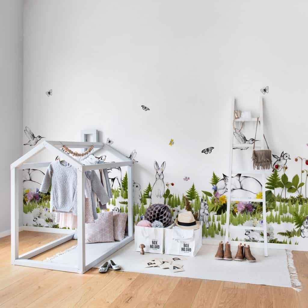 Camera unui copil amenajata cu fototapet cu motive inspirate din natura cu covor alb, elemente de mobilier si incaltaminte