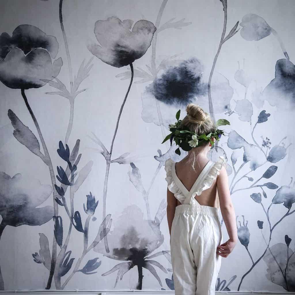 Perete amenajat cu tapet cu motive florare in fata caruia sta o fetita