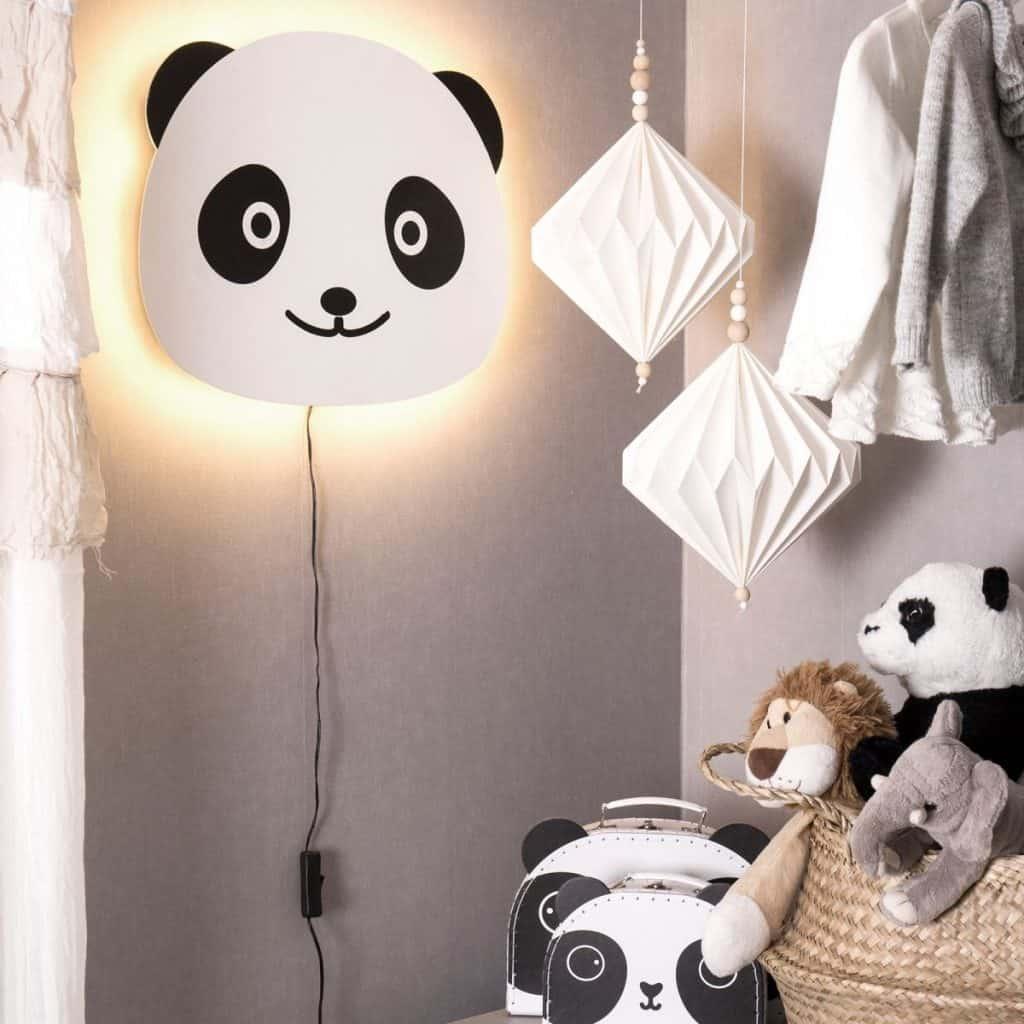 Aplica de perete de forma unui cap de urs panda, langa jucarii si hainute pentru copii