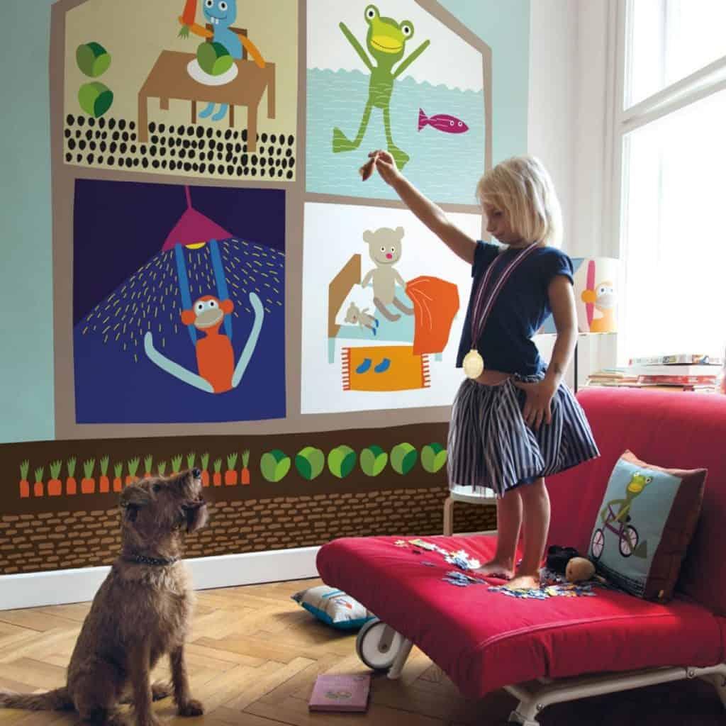 Camera decorata cu fototapet colorat, cu animale, cu o fetita pe o canapea visinie, care se joaca cu un caine
