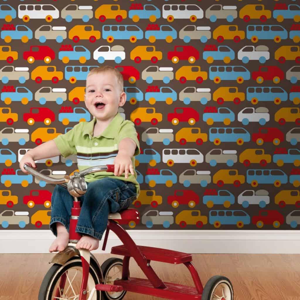 Perete cu tapet cu masinute, in fata caruia se afla un baiat pe o bicicleta rosie