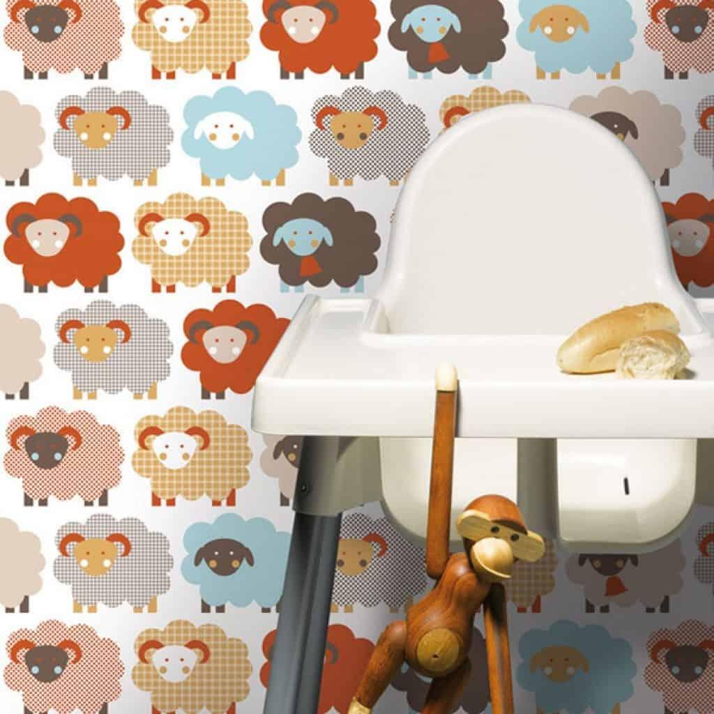 Perete cu tapet imprimat cu oite in fata caruia se afla un scaun pentru copii și o jucarie maimuta