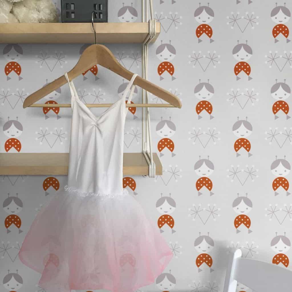 Tapet imprimat cu imprimeuri care reprezinta o fetita si umeras cu o rochita alb cu roz
