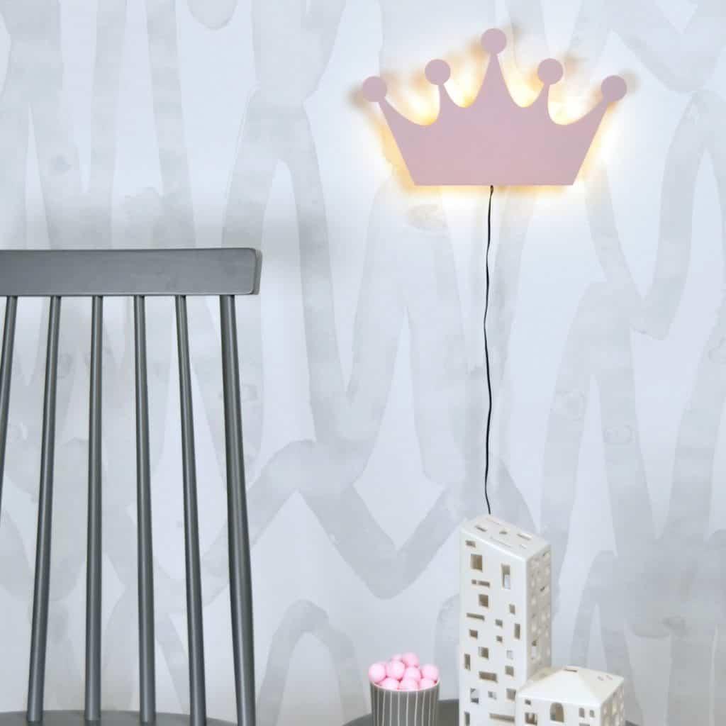 Aplica de perete in forma de coroana roz langa spatarul unui scaun si jucarii