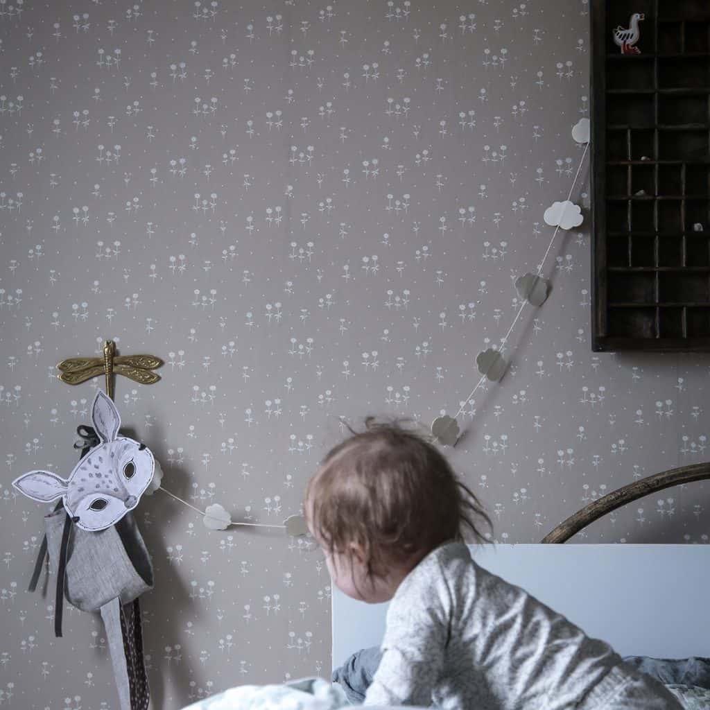 Perete amenajat cu tapet imprimat cu forme albe pe fond bej, intr-o camera cu un bebelus si jucarii