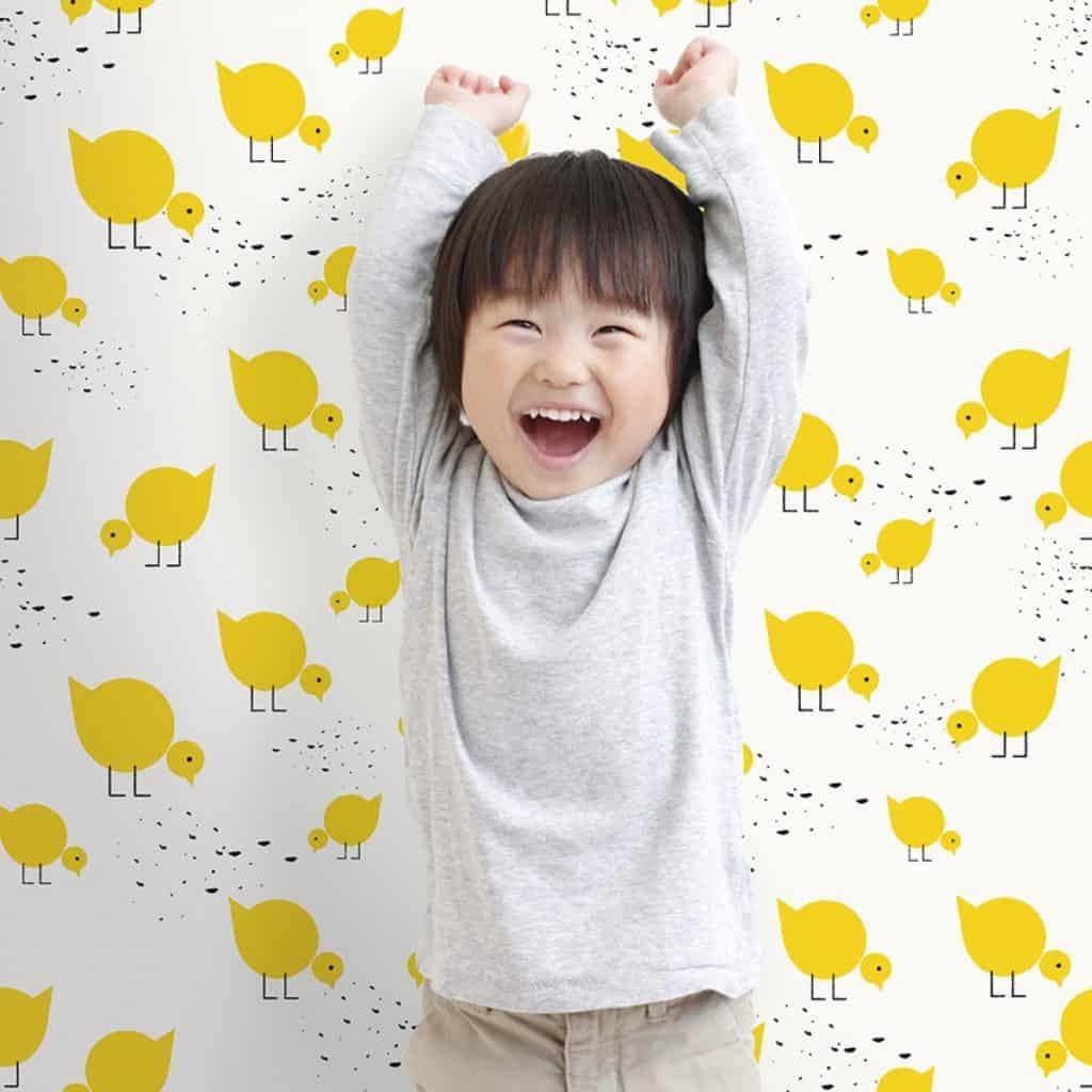 Perete amenajat cu tapet imprimat cu pui galbeni in fata caruia se afla un copil