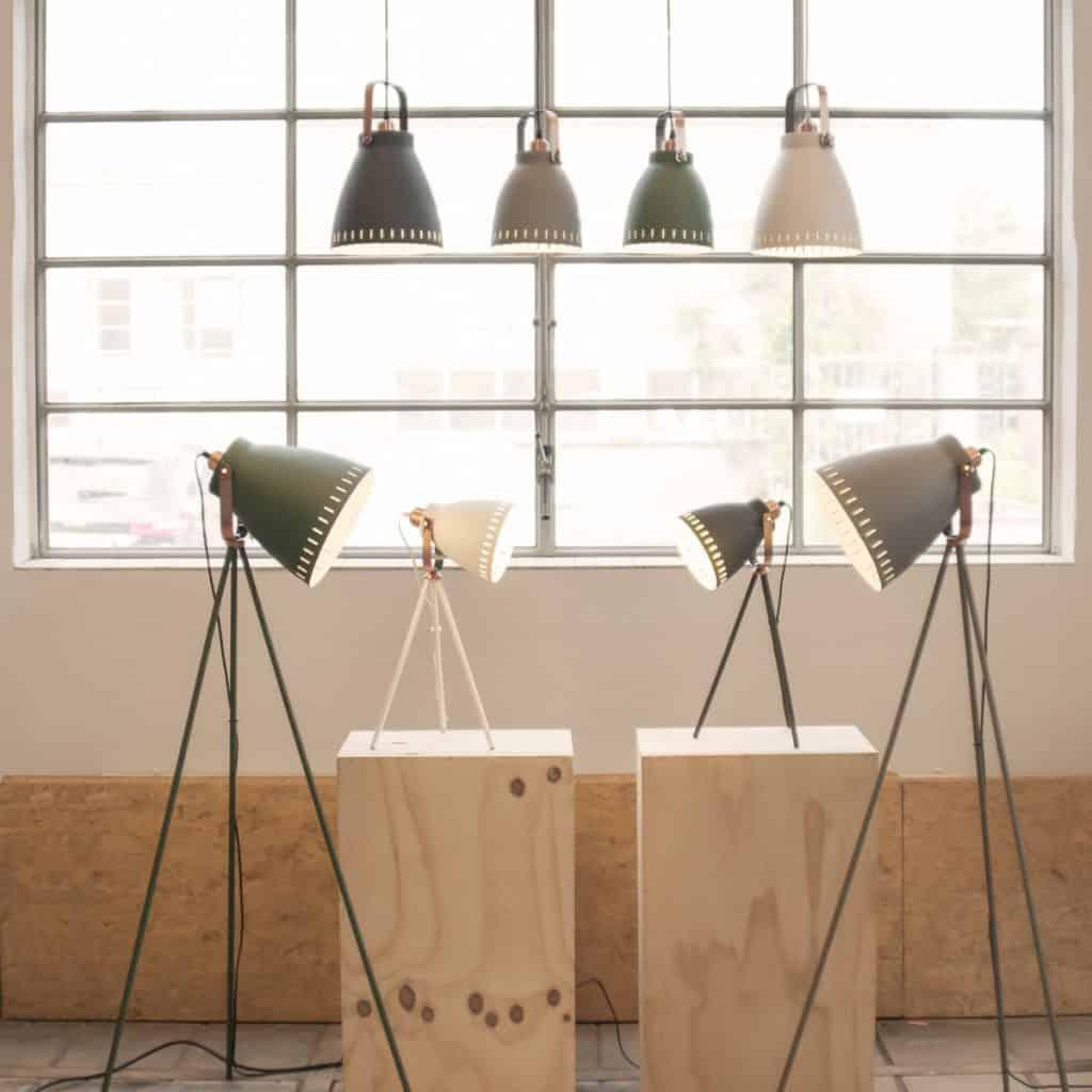 Lampi de birou de diferite culori și picioare de diverse dimensiuni, expuse pe doua postamente din lemn si pe podea, si patru lampi suspendate