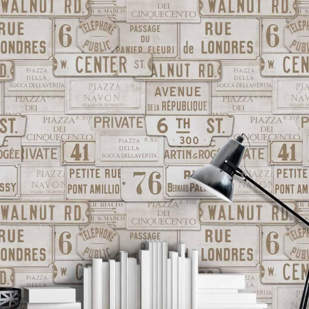 Perete amenajat cu tapet imprimat cu placute indicatoare vintage, in fata caruia se afla carti si o lampa de birou