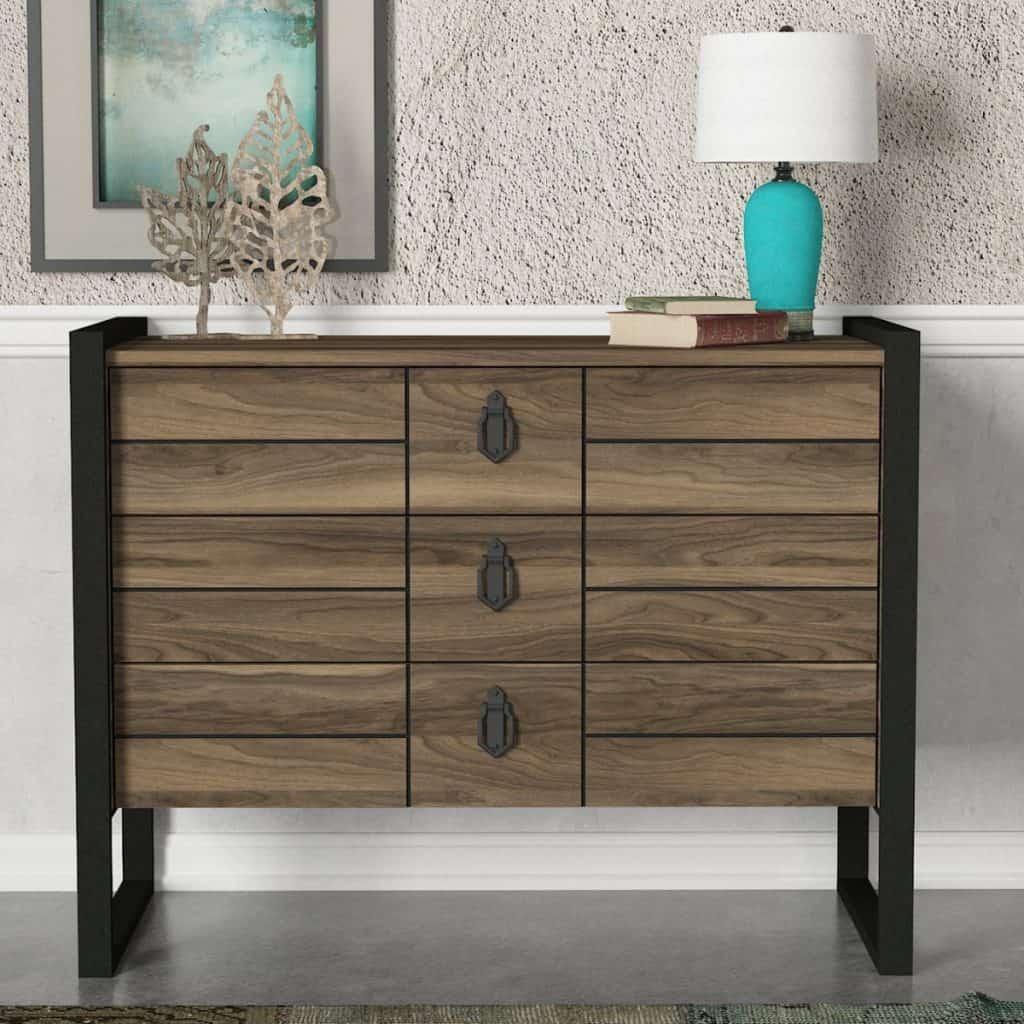 Comoda cu trei sertare, de culoarea lemnului, pe care se afla obiecte decorative