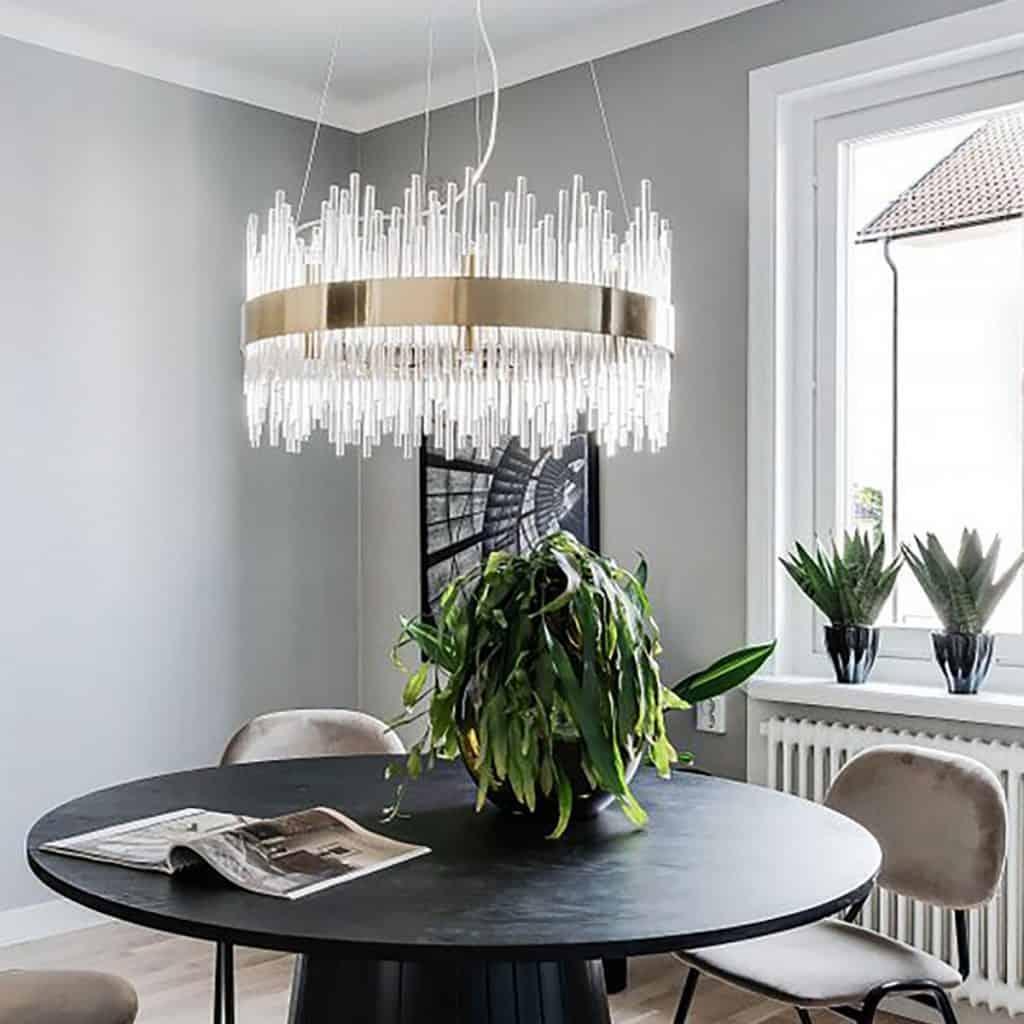 Lampa suspendata realizata din tuburi de sticla, deasupra unei mese cu scaune si plante decorative