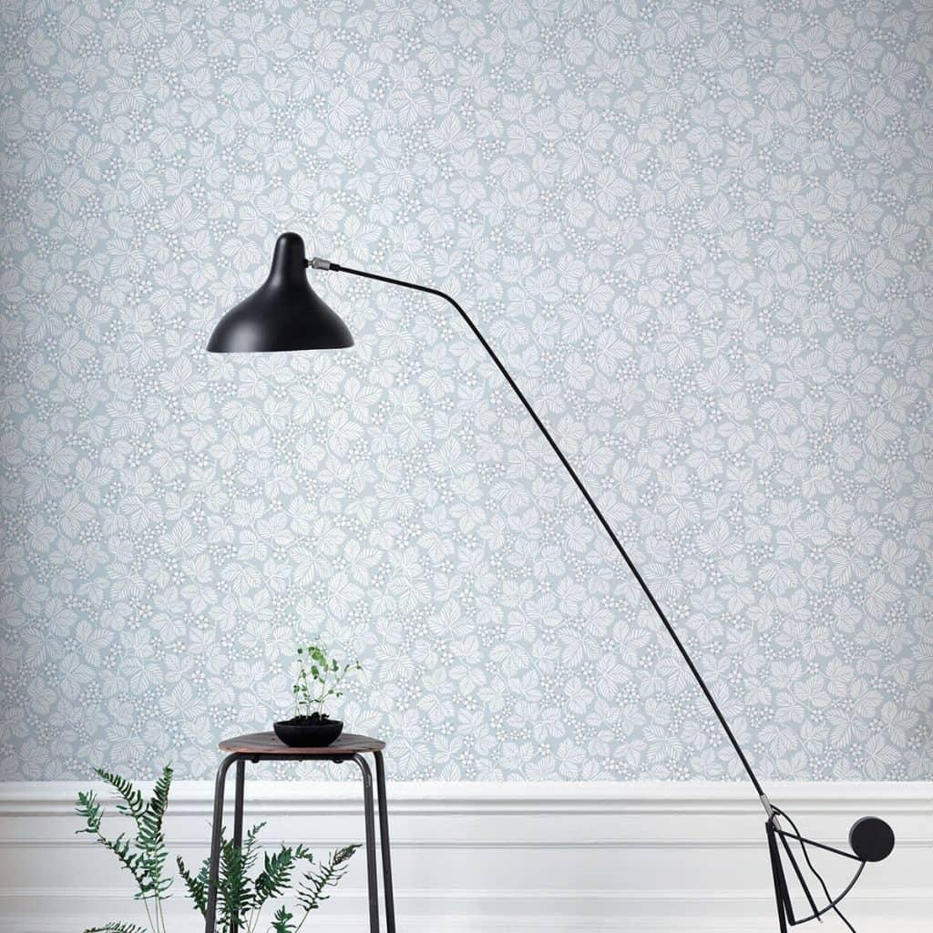 Perete amenajat cu tapet cu imprimeuri albe pe fond albastru deschis, in fata caruia se afla o lampa, un scaun si plante decorative