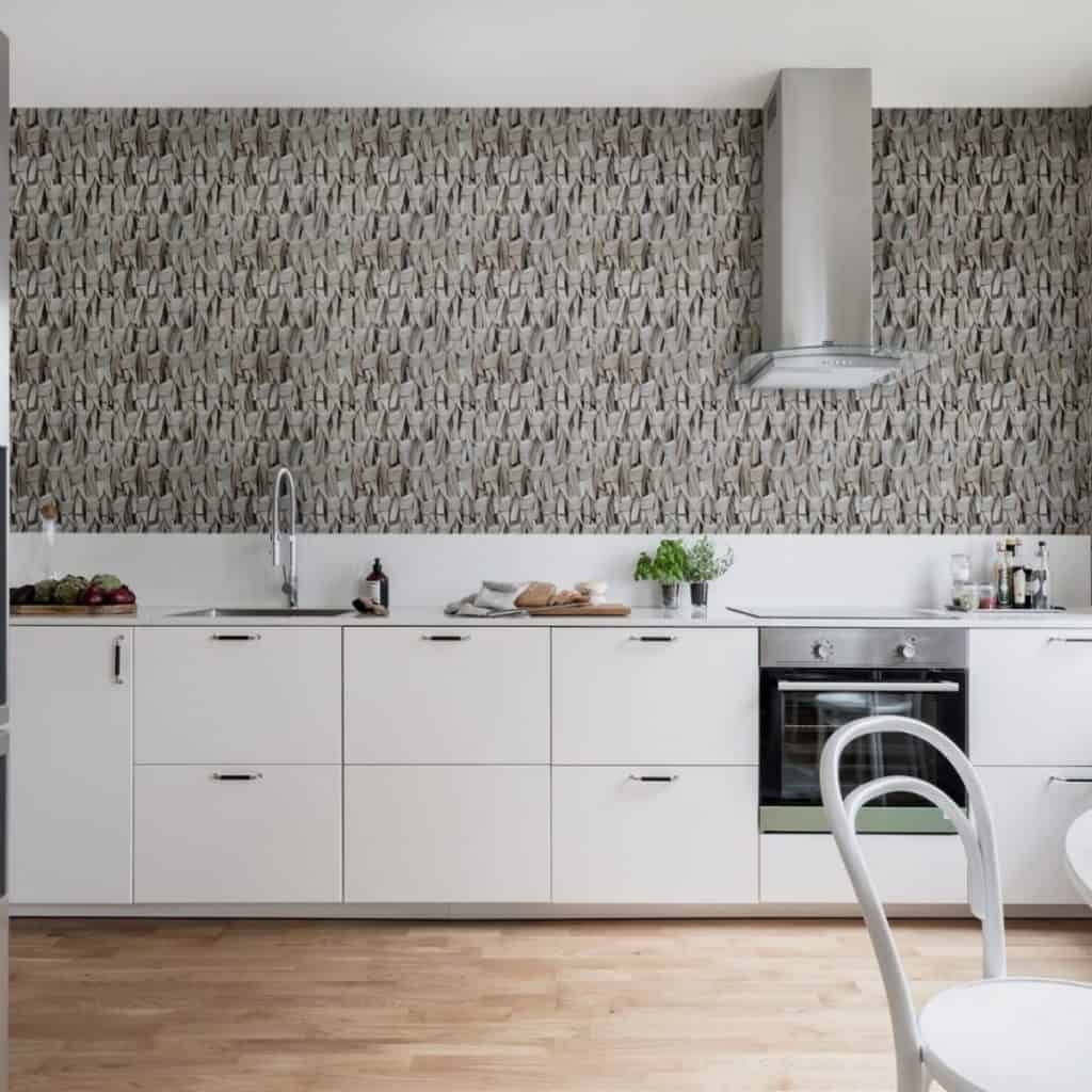 Bucătărie cu mobilă alba, cuptor negru, hota si pereti cu fototapet reprezentand o impletitura de frunze uscate