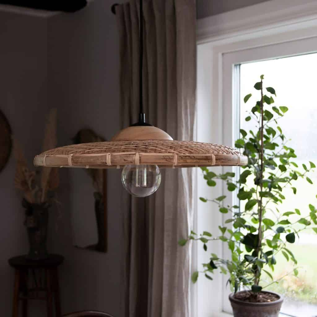 Lampa suspendata din ratan intr-o incapere cu planta decorativa asezata in fata unei ferestre