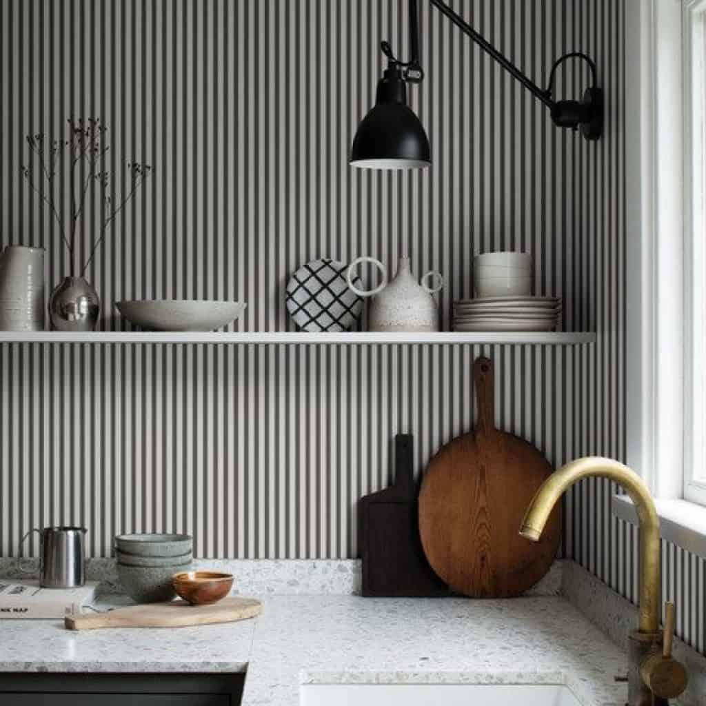 Bucatarie cu tapet cu dungi verticale alb si gri, raft alb cu vase de bucatarie, tocatoare din lemn si blat din granit