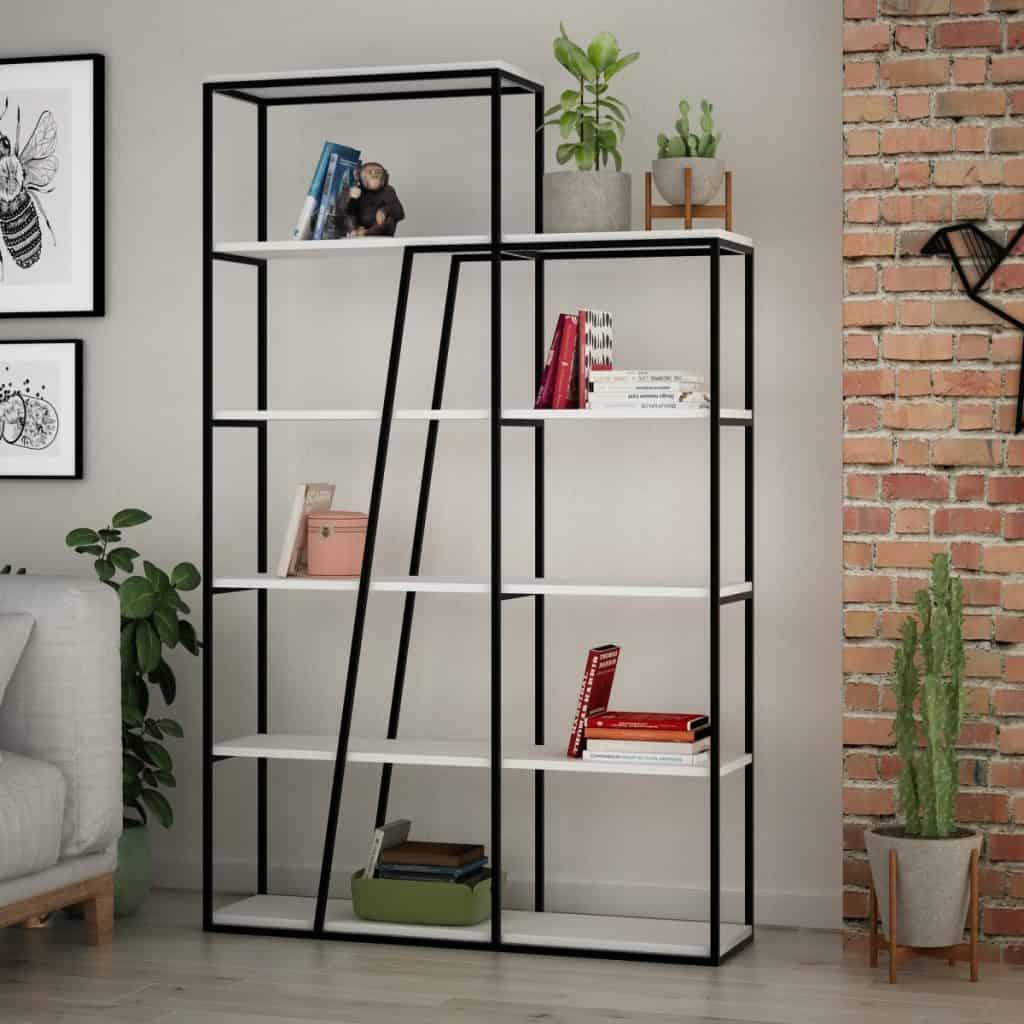 Biblioteca cu carti, plante si obiecte decorative intr-un living cu tablouri, fotoliu si un perete accent din caramida