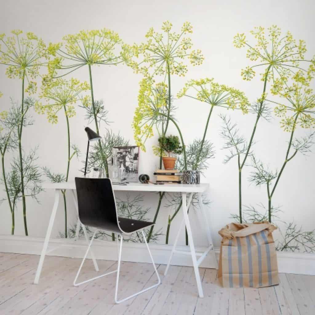 Perete cu fototapet cu frunze si flori de marar, in fata caruia de afla o masa cu lampa si diverse obiecte, scaun si o punga din hartie