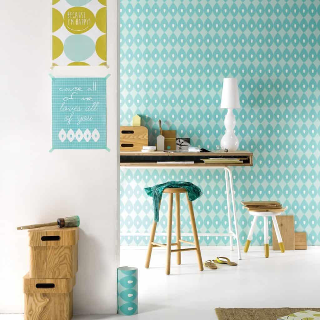 Camera cu tapet in nuante de albastru si alb, cu masa cu lampa alba si obiecte de birotica, doua scaune si doua cutii de depozitare din lemn