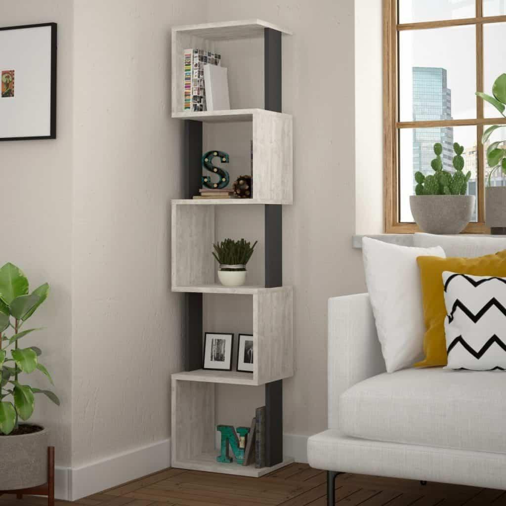 Bibliotecă deschisa la culoare in coltul unui living cu fereastra cu planta decorativa, canapea alba pe care se afla trei perne