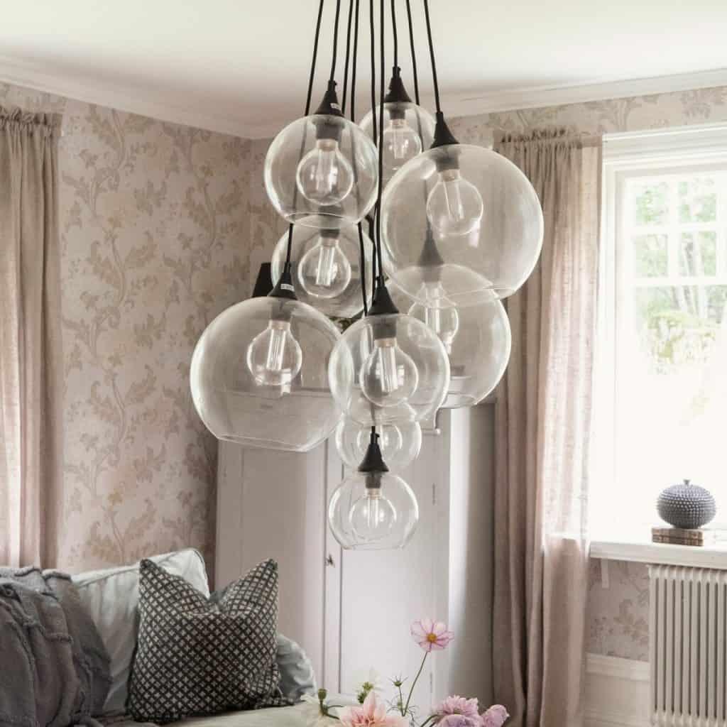 Lampa suspendata cu 9 globuri de sticla, intr-un living cu fereastra, dulap alb si canapea cu perna decorativa