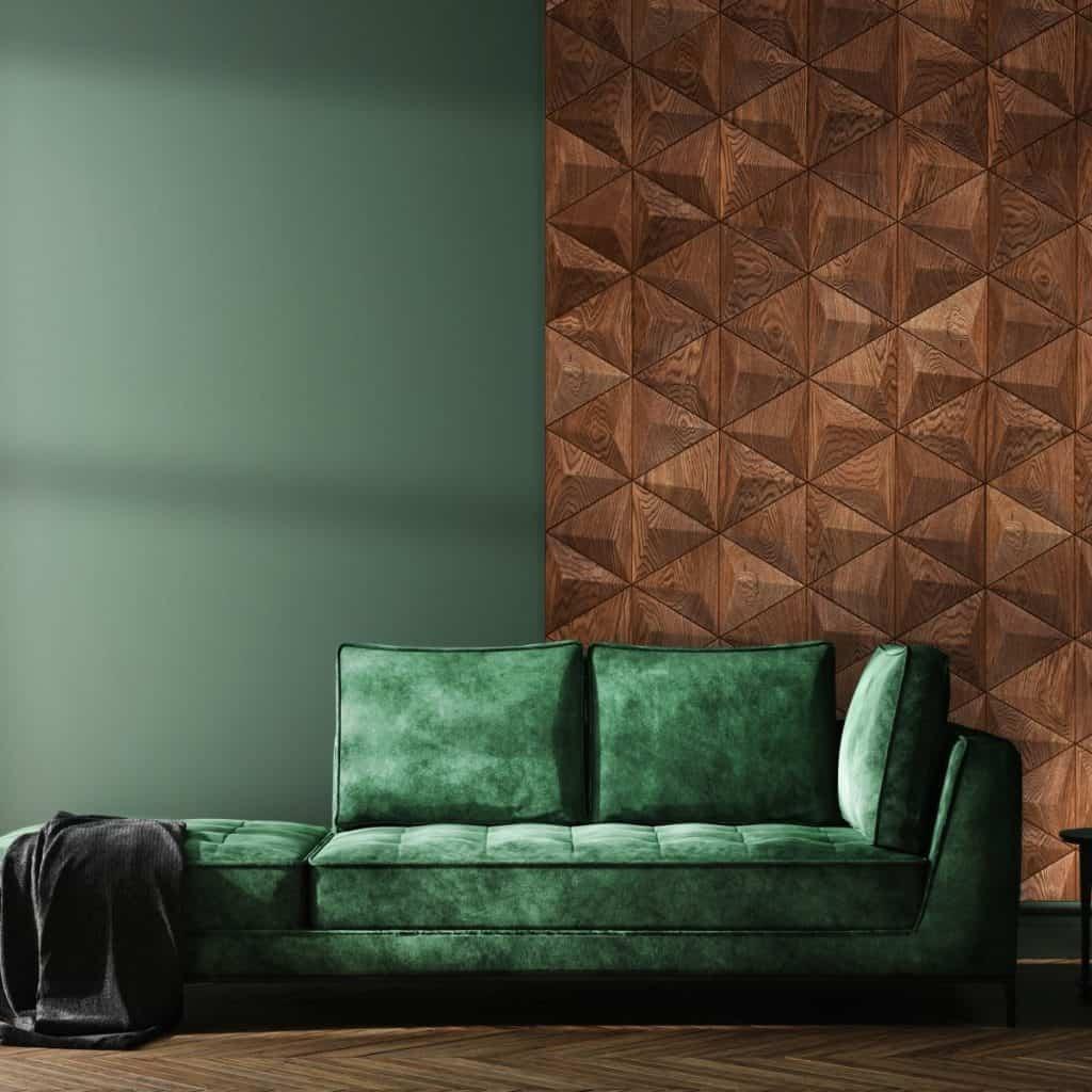 Perete cu panouri decorative din lemn in fata caruia se afla o canapea verde