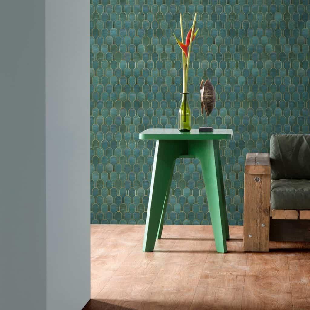 Alt text: Perete cu tapet in nuanțe de turcoaz, cu o masa verde in fata, pe care se afla o planta si o canapea
