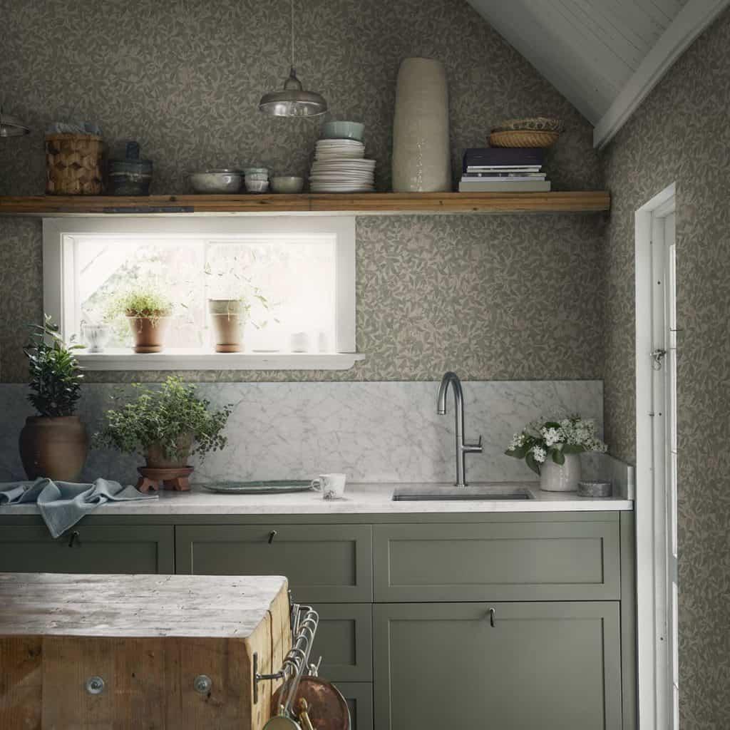 Tapet Linnea Garden Green intr-o bucatarie cu mobila alb cu gri, polita cu vase, plante decorative si o insula din lemn