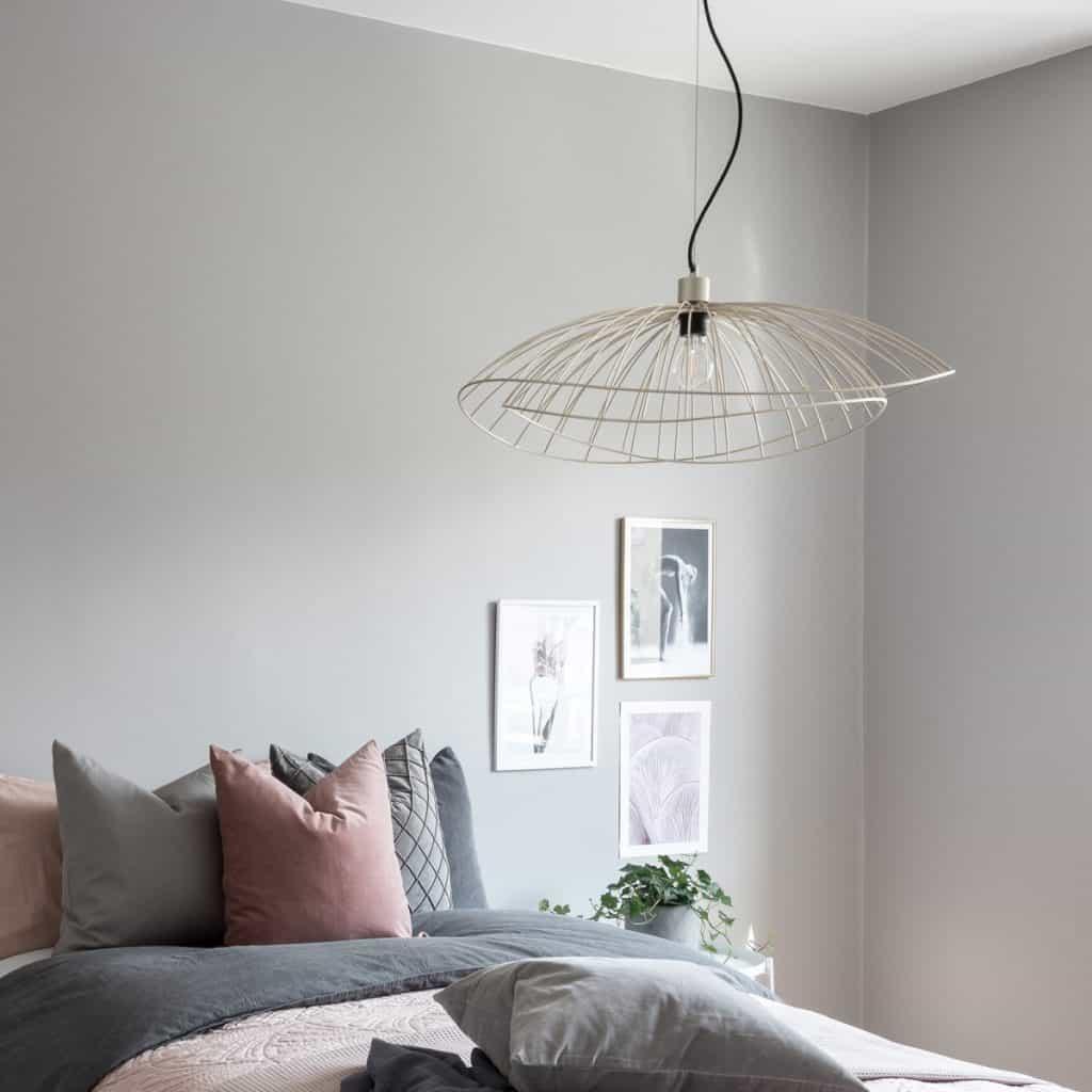 Lustra Ray intr-un dormitor cu pat si perne, cu trei tablouri si o planta decorativa