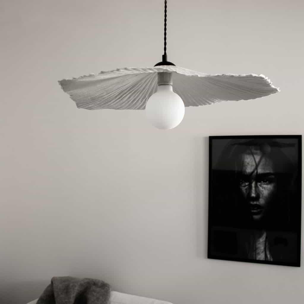Lampa suspendata Tropez, intr-o camera cu un tablou alb-negru, cu chipul unei femei