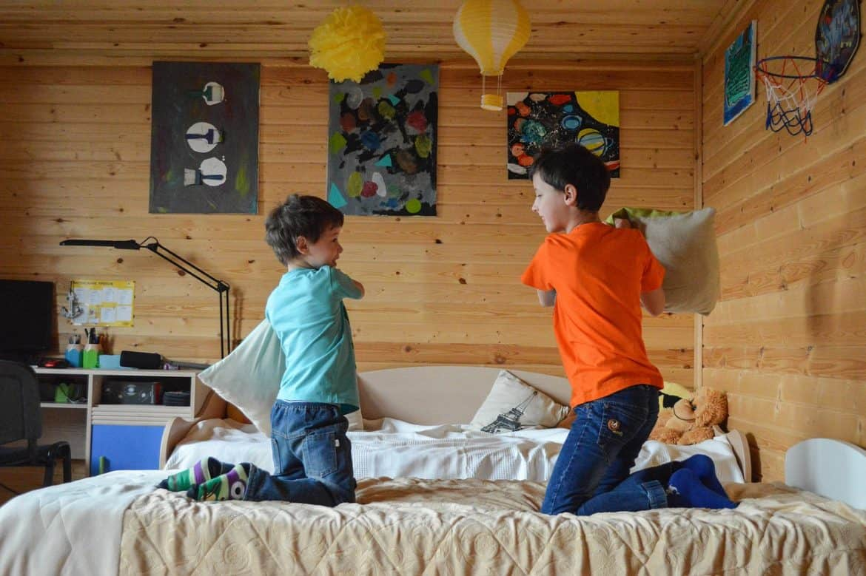 camera de baieti decorata in uante pamantii si cu un pat pe care se bat cu perne doi copii