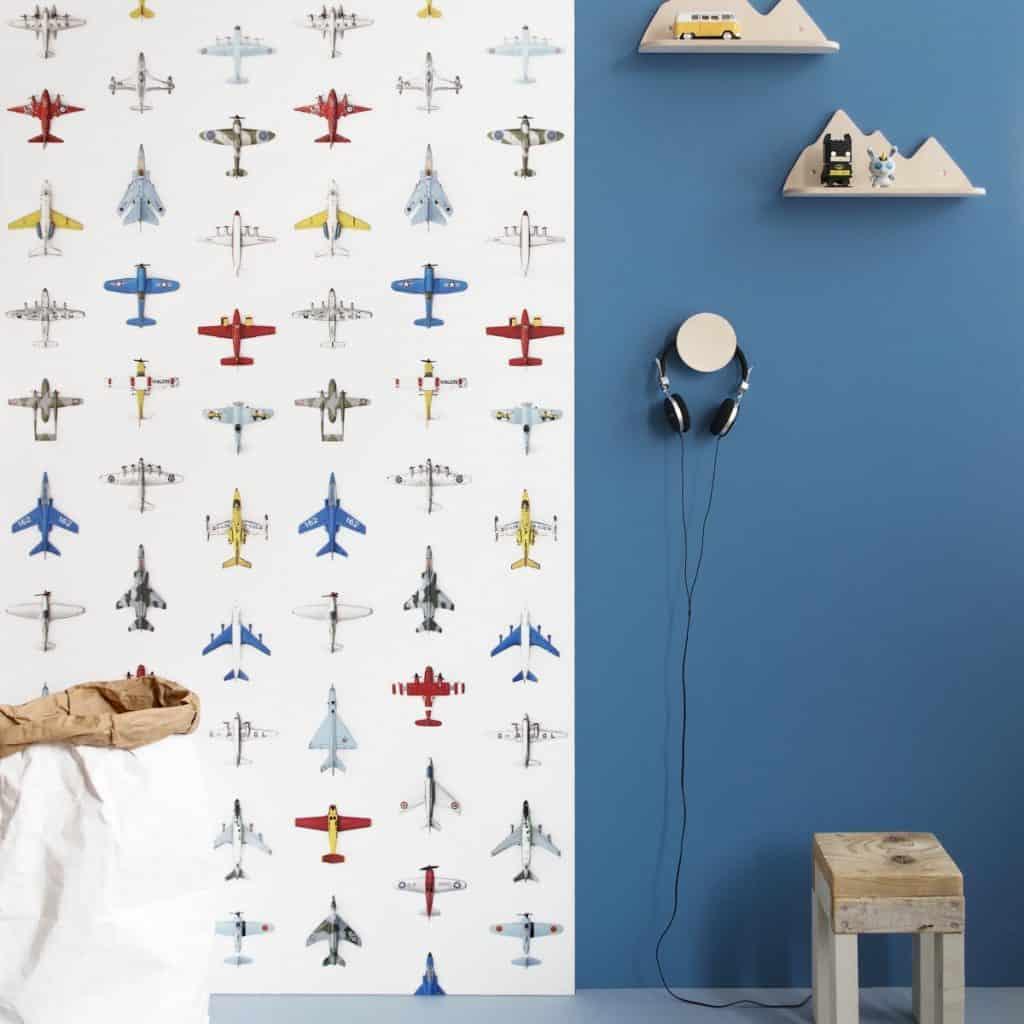 Tapet Airplanes pe un perete pe jumatate vopsit cu albastru, unde sunt doua polite cu jucarii si o pereche de casti, iar in fata peretelui se afla un scaun din lemn