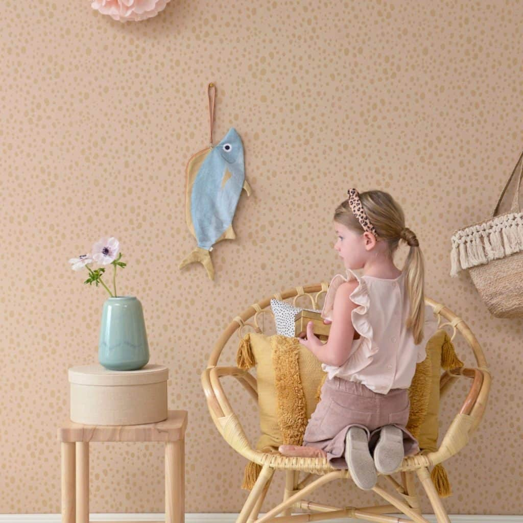 Tapet Animal Dots intr-o camera cu un fotoliu pe care sta in genunchi o fata, cu un suport pe care se afla o cutie si un  vas cu floare si cu un peste din material textil agatat pe perete