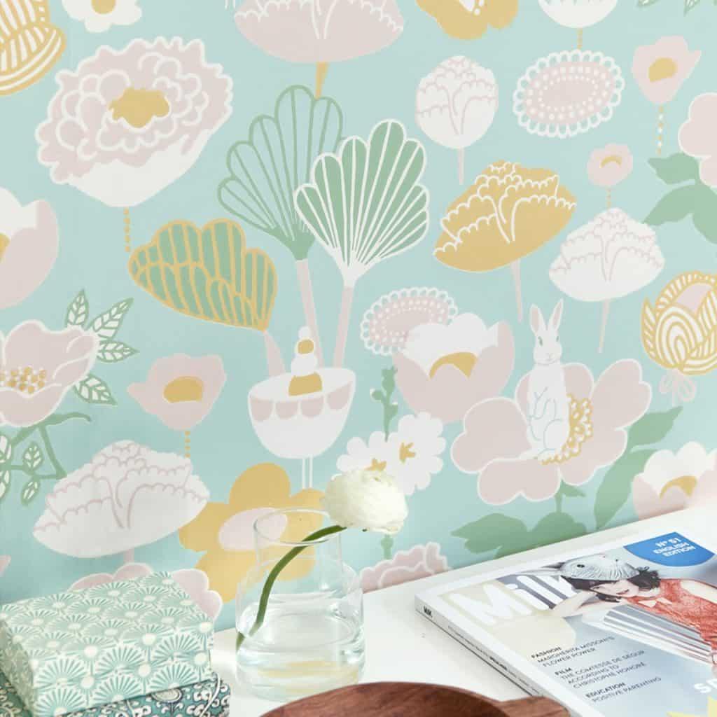 Tapet Little Light in fata caruia se afla o masa cu o revista, un vas cu floare si doua cutii