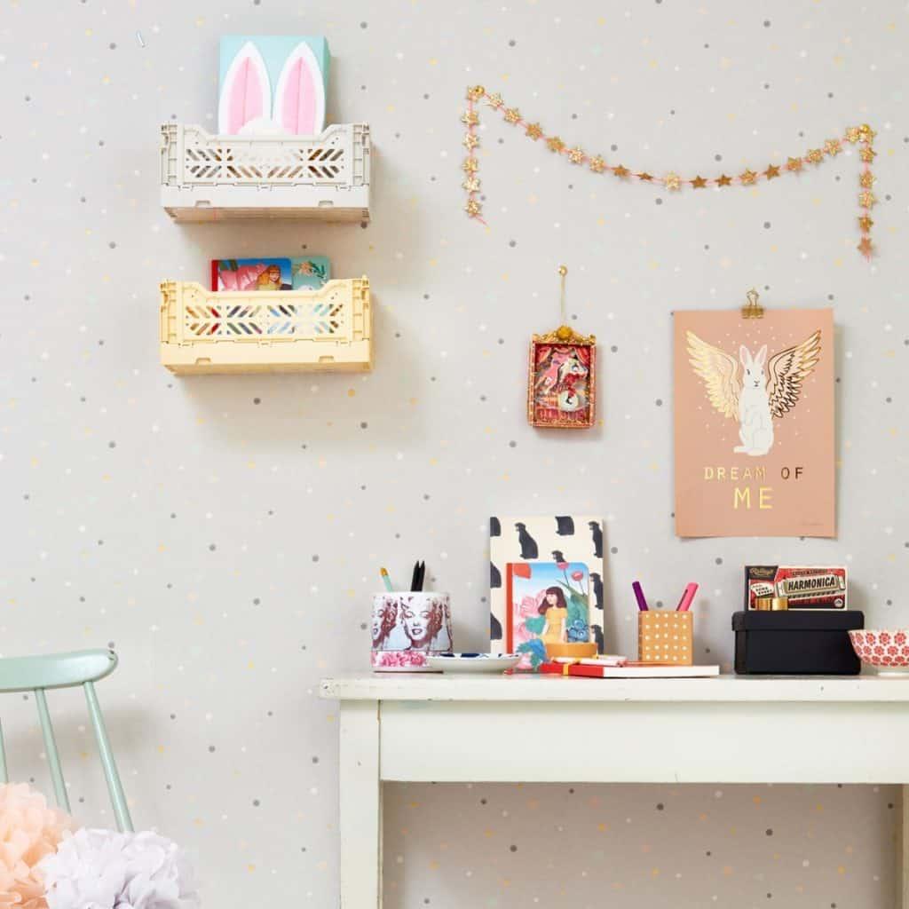 Tapet Stardust intr-o camera cu masa alba pe care se afla rechizite si obiecte decorative, cu doua tablouri, doua polite cu jucarii si o ghirlanda